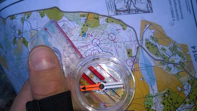 Kartanlukua. Kun kompassin punainen neula on karttapohjoista kohti, kartta on maaston suuntaisesti.