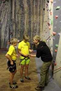Kiipeilyareenan Oskari opastaa 14-vuotiaita Antonia (vas.) ja Jaakkoa varmistinköyden kiinnittämisessä.