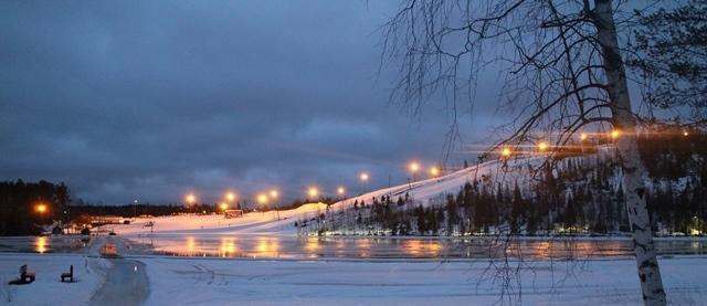 Näkymä mökkikylästä Häkärinteille. Jään kestäessä mökkikylästä rinteeseen pääsee näppärästi jäätä pitkin. Talvella lammen ympäri kulkee hiihtoreitti ja jäälle aurataan matkaluistelurata. Kuva: KivaaTekemistä.fi