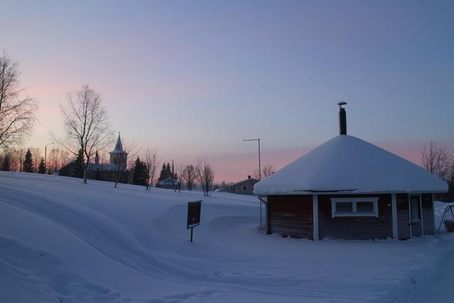 Lomamaja Pekosen kota, taustalla Muonion kirkko. Kuva: KivaaTekemistä.fi